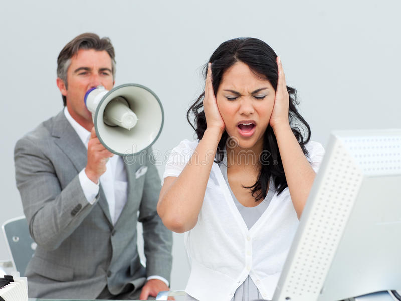 Furious manager shouting through a megaphone. In a colleague's ears in the office stock photos