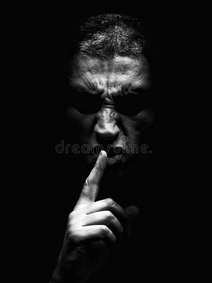 Furious mature man with an aggressive look making the silence sign in a violent and threatening way. royalty free stock images