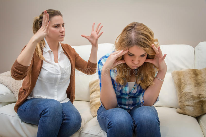 Furious mother arguing with her âEUR. Furious young mother in a discussion with her teenage daughter. Problems between generations concept stock images