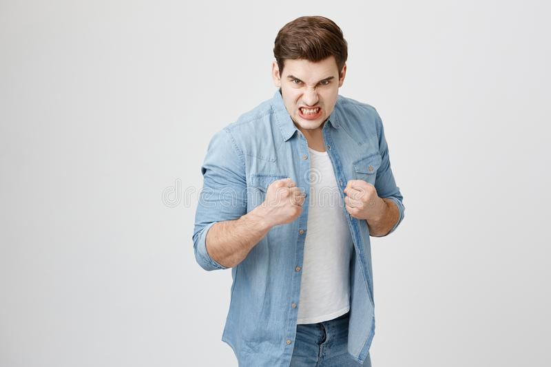 Furious muscular european male model in denim shirt with trendy haircut holding fists in front of him as if ready for. Fight or any challenge, clenches teeth stock photography