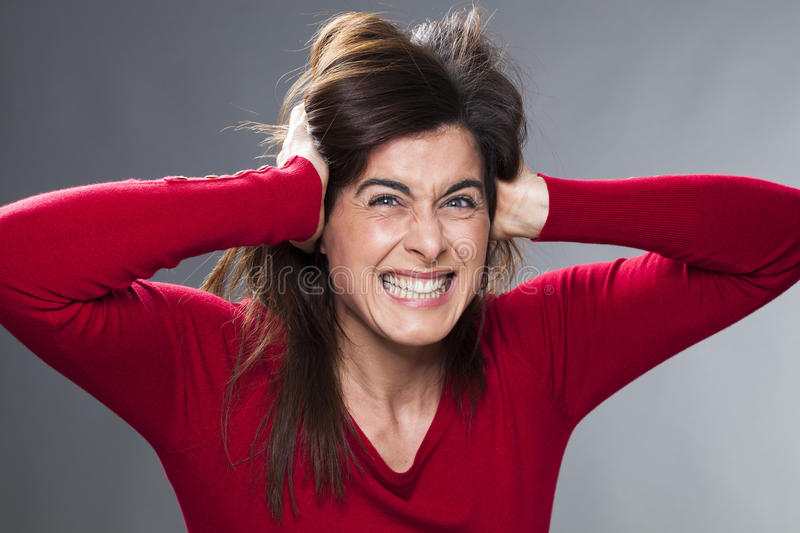 Furious 30's brunette suffering from severe headache. Furious young woman having painful headache, covering closed ears, annoyed by loud noise, ignoring someone stock photo