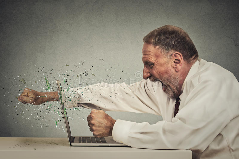 Furious senior businessman throws punch into computer. Screaming isolated grey office wall background. Negative human emotions, facial expressions, feelings stock photography