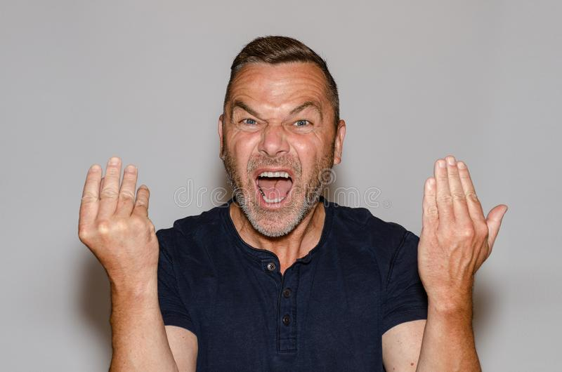 Furious man yelling at the camera. Furious vehement middle-aged man yelling at the camera gesturing with his hands in rage in a communication concept against a royalty free stock photo