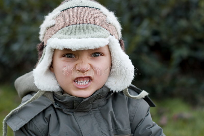 Furious Winter Boy. Portrait of an angry young boy in winter outerwear, taken outdoors royalty free stock photos