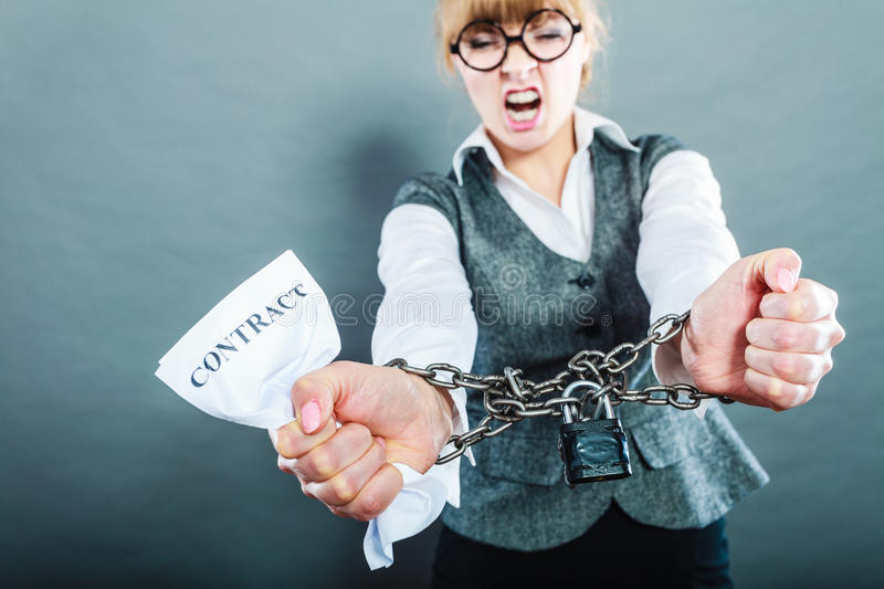 Furious woman with chained hands and contract. Business and stress concept. Furious businesswoman in glasses with chained hands holding contract grunge stock images