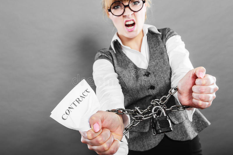 Furious woman with chained hands and contract. Business and stress concept. Furious businesswoman in glasses with chained hands holding contract grunge royalty free stock images