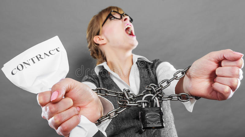 Furious woman with chained hands and contract. Business and stress concept. Furious businesswoman in glasses with chained hands holding contract grunge royalty free stock photo