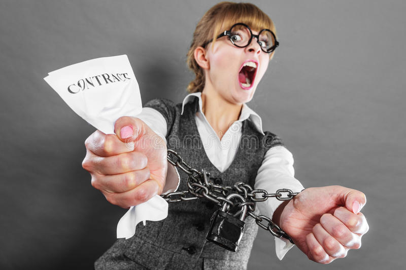 Furious woman with chained hands and contract. Business and stress concept. Furious businesswoman in glasses with chained hands holding contract grunge royalty free stock photography