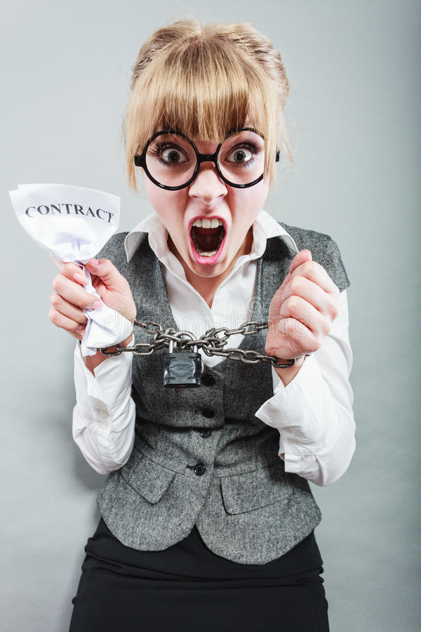 Furious woman with chained hands and contract. Business and stress concept. Furious businesswoman in glasses with chained hands holding contract grunge stock photo