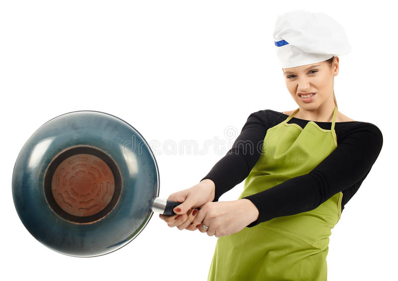 Furious woman cook hitting with the frying pan. Angry woman cook hitting hard with the frying pan royalty free stock photography