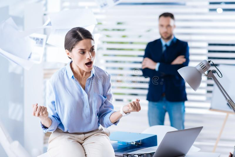 Angry woman clenching her fists and shouting while being furious. Furious woman. Emotional angry young women sitting on the table and clenching her fists while stock image