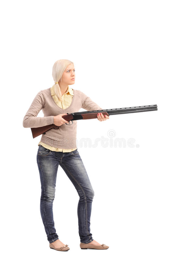 Furious woman holding a shotgun. Full length portrait of a furious woman holding a shotgun isolated on white background stock images