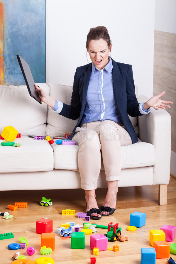 Furious woman in a room full of kids toys royalty free stock photography
