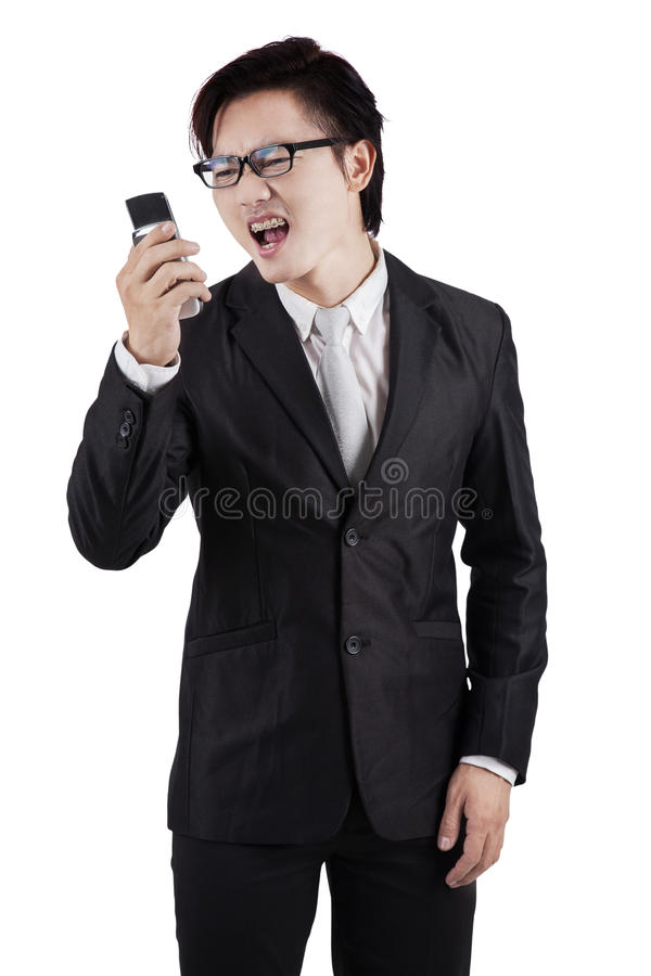 Furious worker screaming on his cellphone. Portrait of furious businessman wearing formal suit and yelling on his cellphone, isolated on white royalty free stock photography