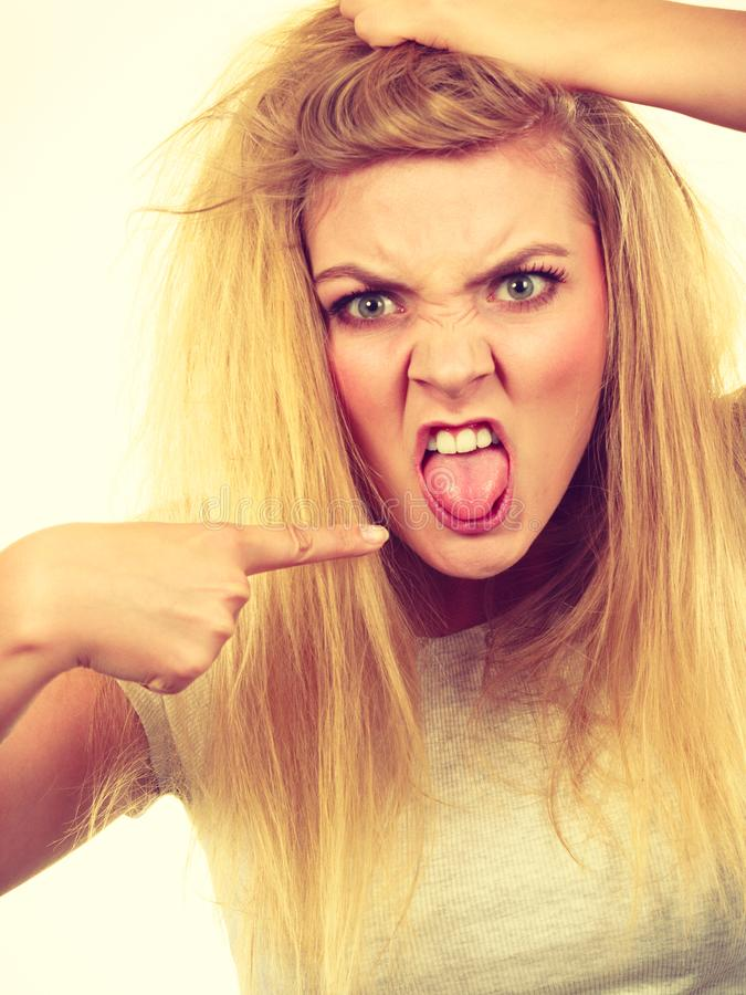 Furiously mad hungry blonde woman holding hair royalty free stock photography