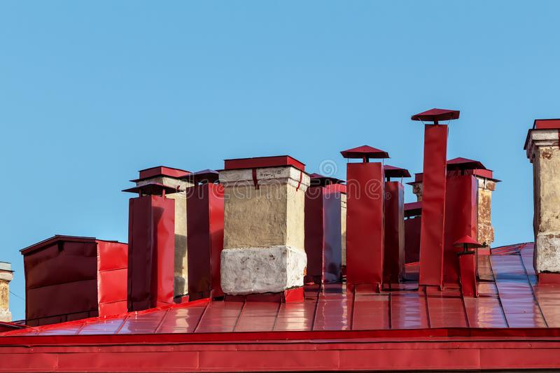 Furnace and ventilation pipes on the red roof stock image