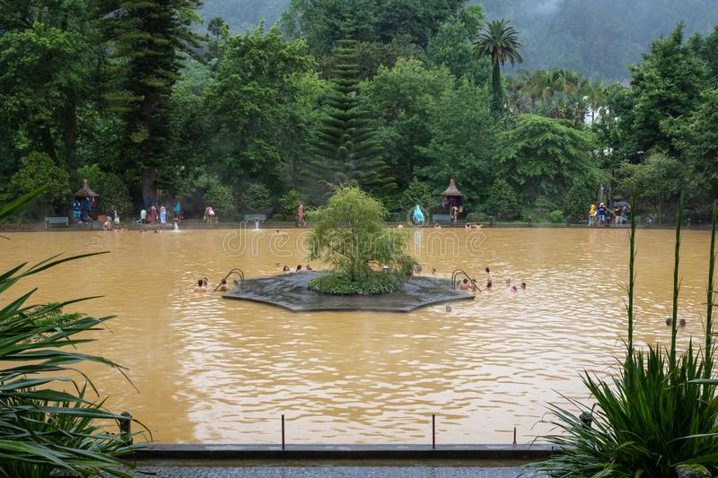 People swimming in mineral thermal pool in the Terra Nostra botanical garden at Furnas, Sao Miguel island, Azores, Portugal. Furnas, Azores, Portugal -  August stock photos