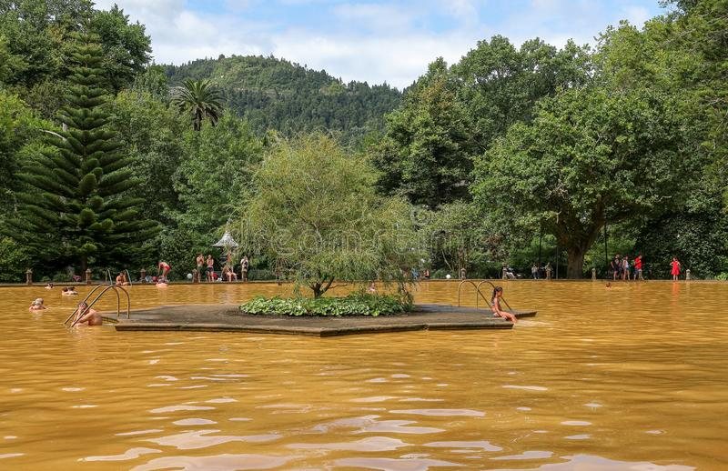 People swimming in a mineral thermal pool in the Terra Nostra botanical garden at Furnas, SãoMiguel island, Azores. Furnas, Azores, Portugal - Septembre 15 stock image