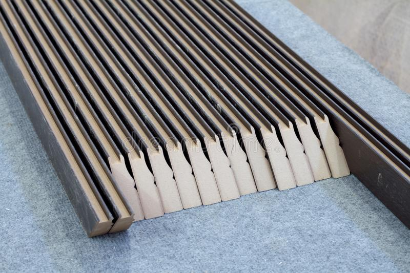 Furniture accessories. Manufacture of skirting boards in a furniture factory. Furniture accessories. Colorful wooden floor for home renovation. Manufacture of royalty free stock photo