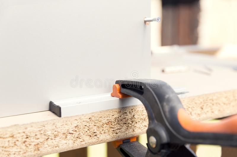 Furniture assembly. Making of kitchen cabinet using construction clamp and screws stock photo