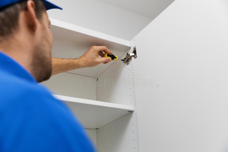 Furniture assembly service - worker installing cabinet doors royalty free stock photos