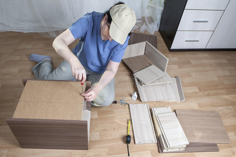 Furniture assembly, woman fastens sheet hardboard in back bedside table. stock photo