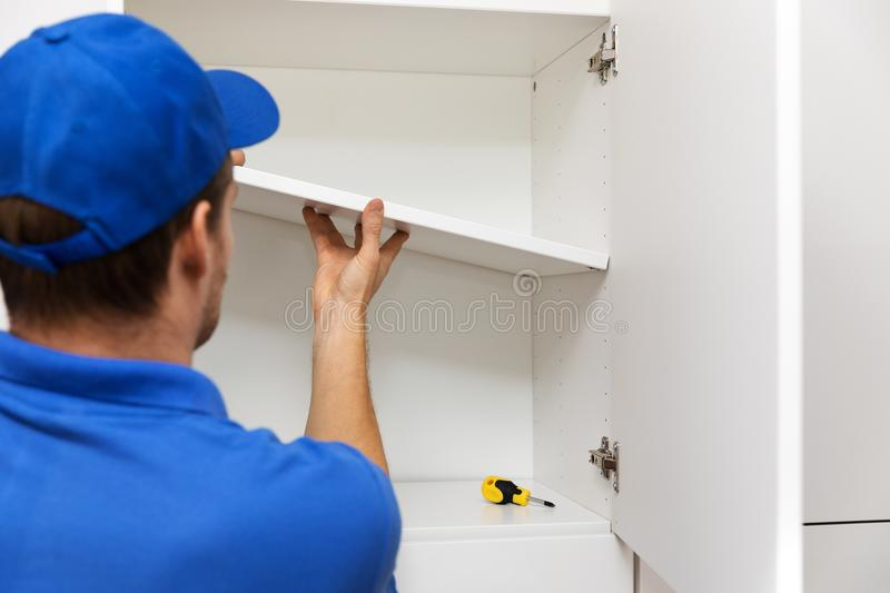 Furniture assembly - worker installing cabinet shelf stock images