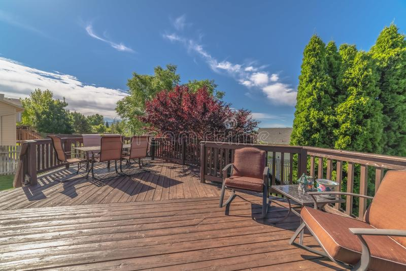 Furniture on the balcony of home with brown wooden floor railing and stairs. The outdoor living space has a scenic view of the yard, trees, and blue sky on a stock images