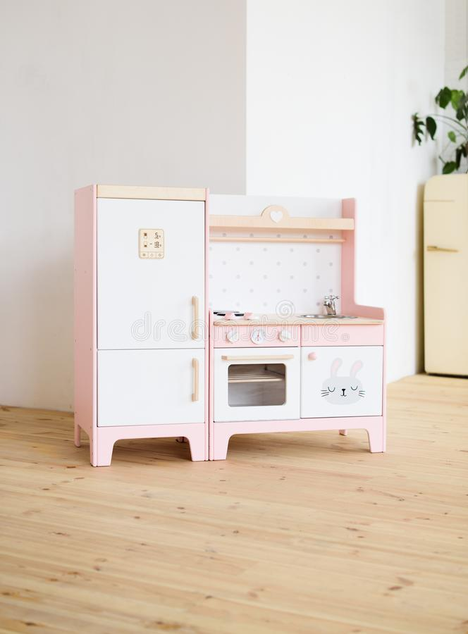 Furniture for children. Sweet little pink kitchen with fridge, stove, oven and sink in light room stock images