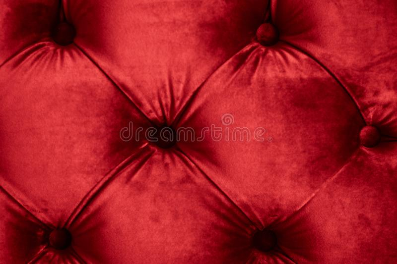 Red luxury velour quilted sofa upholstery with buttons, elegant home decor texture and background. Furniture design, classic interior and royal vintage material royalty free stock photography