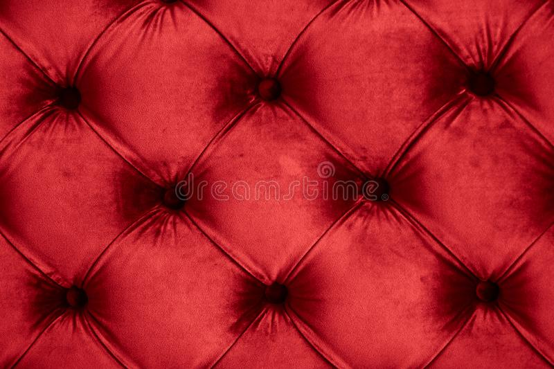 Red luxury velour quilted sofa upholstery with buttons, elegant home decor texture and background. Furniture design, classic interior and royal vintage material stock photos