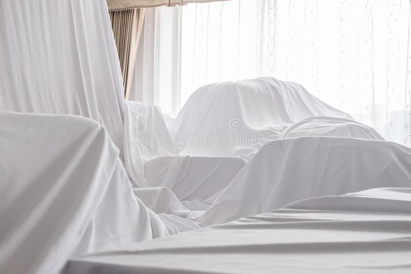 Furniture Dust Covers. White dust cover cloth covering furnitures in a room stock image
