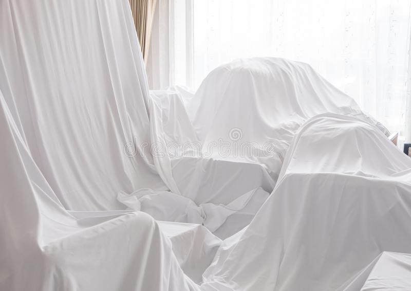 Furniture Dust Covers. White dust cover cloth covering furnitures in a room stock photo