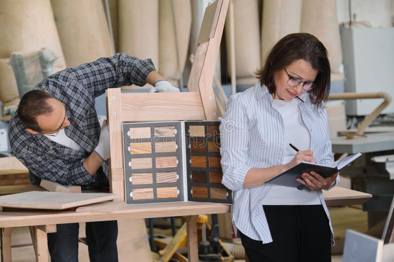 Furniture joinery production, working male joiner and female designer with wood samples choosing finishing. Writing in business notebook royalty free stock photo