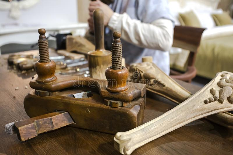 Furniture manufacturing with joiner tools, wooden decorative elements and carpenter, working with chisel at the background. royalty free stock photo