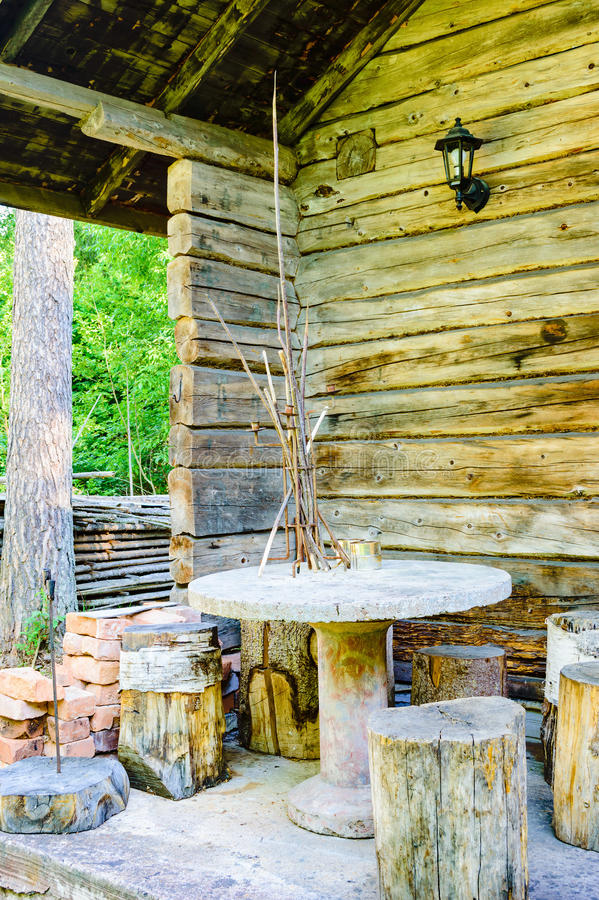 Furniture. Outdoor furniture made of cut timber, concrete and other materials. Furniture is placed on a porch outside a cabin in the woods. Cabin is timbered royalty free stock photography