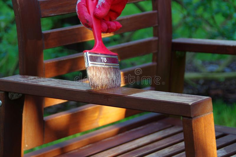 Furniture painting. Garden furniture brush painting. Hand painting the wooden chair outdoor stock image