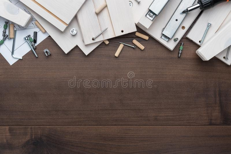 Furniture piece parts and tools on the wooden table with copy space during assembly process royalty free stock photography