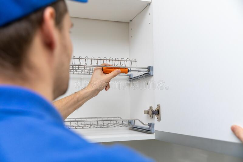 Furniture service worker screwing kitchen cabinet dish rack stock images
