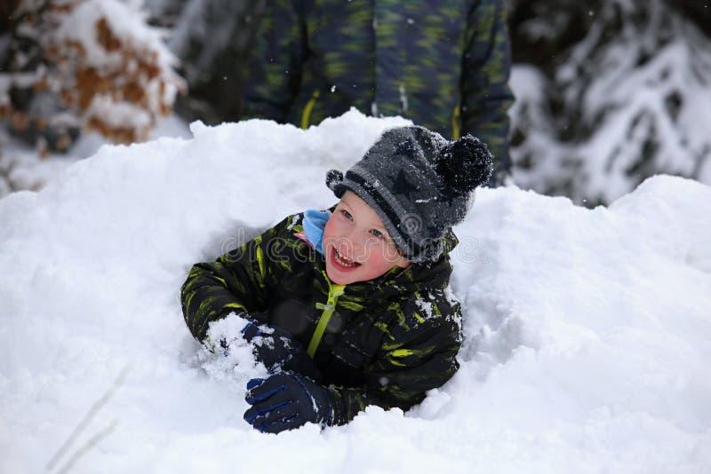 Furo de escavação do menino feliz fora da pilha da neve fotografia de stock royalty free