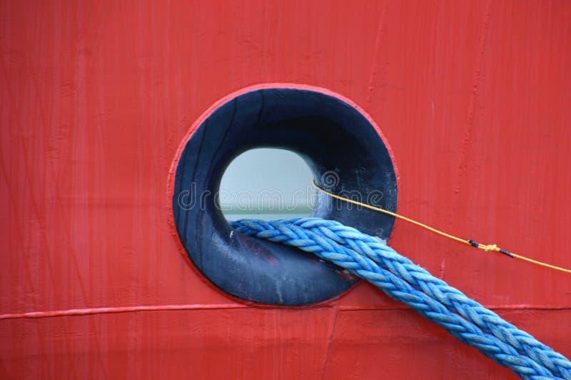 Furo de Hawse em um metal vermelho do navio com um cabo azul que sai fotografia de stock royalty free