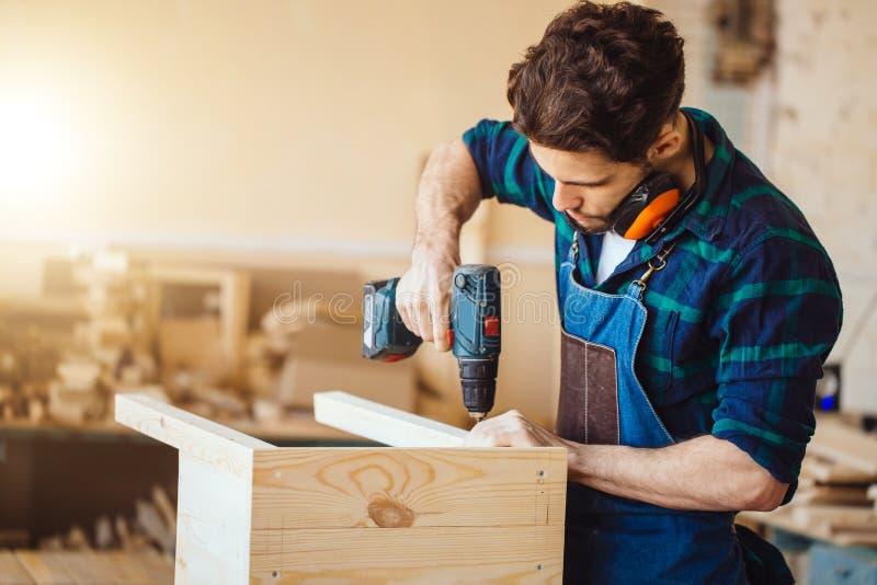 Furo de perfuração disponivel da broca da perfuração de madeira na barra de madeira fotos de stock royalty free
