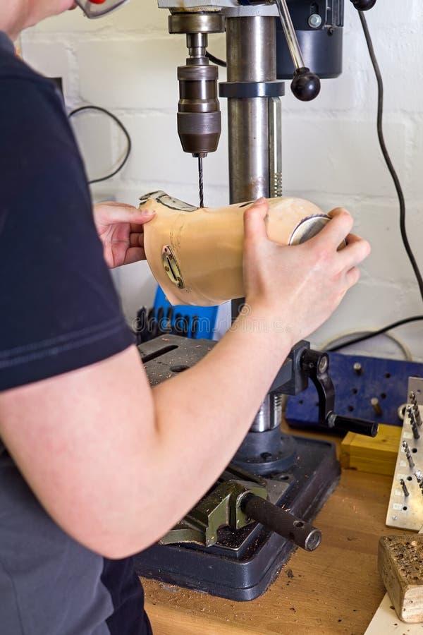 Furo de perfuração do técnico no membro protético foto de stock
