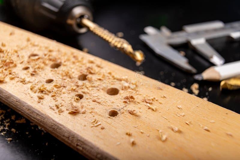 Furo em uma parte de madeira de planeamento seca Os furos fizeram na oficina com uma chave de fenda fotografia de stock
