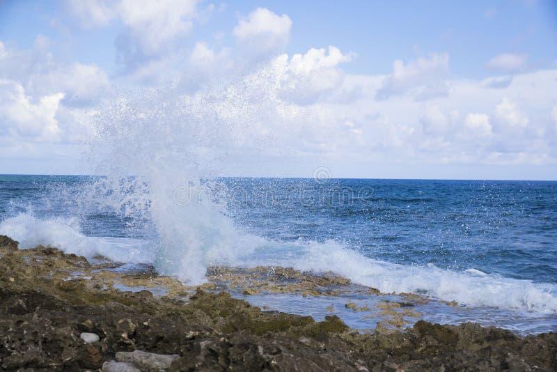 Furo horizontal do sopro na ilha de Grand Cayman com pulverizador de mar imagem de stock