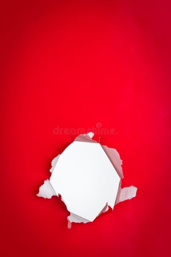 Furo no fundo de papel vermelho fotos de stock