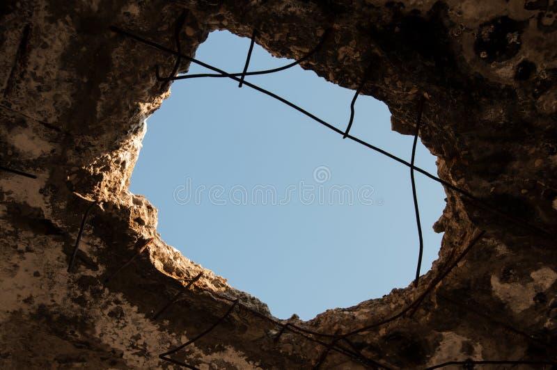 Furo no teto Vista do céu azul que vê completamente o furo no concreto fotografia de stock