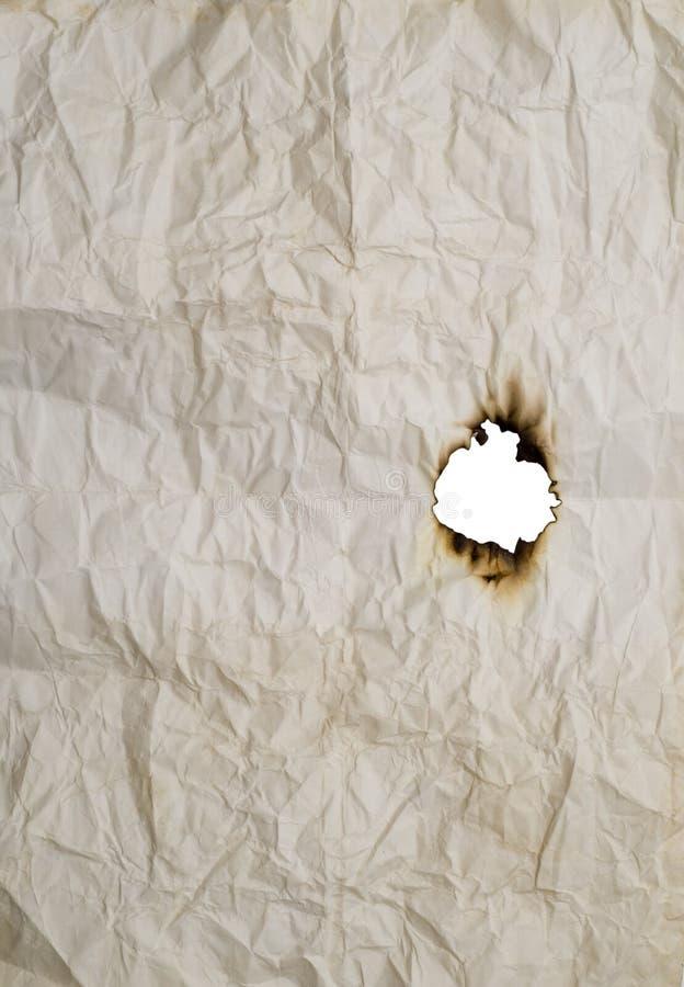Furo queimado no papel enrugado imagens de stock
