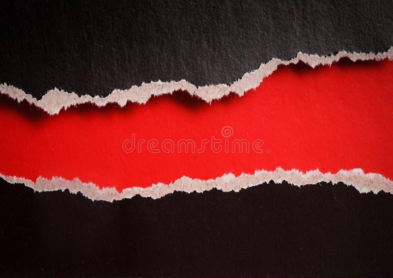 Furo vermelho com bordas rasgadas no papel preto foto de stock