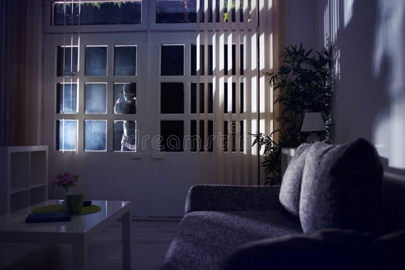Furto con scasso che si rompe in una casa alla notte immagine stock libera da diritti